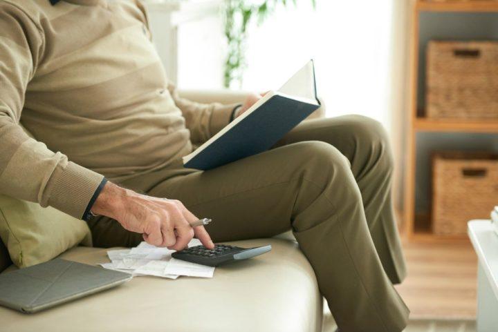 homem sentado usando uma calculadora